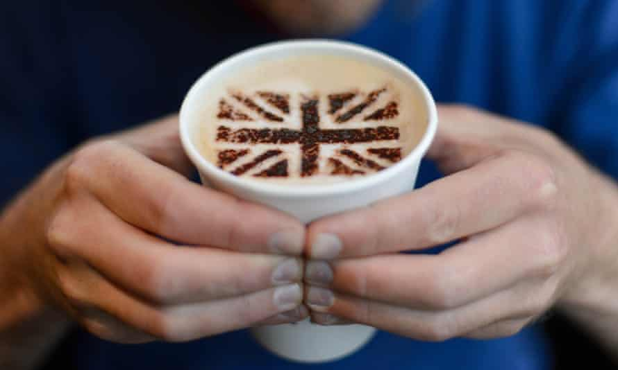 A man holds a cup of coffee with a Union Flag symbol in the foam