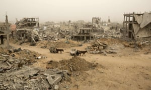 Palestinians ride donkey carts during a sandstorm on February 11, 2015 next to buildings destroyed during last year's 50-day war between Israel and Hamas-led militants, in Gaza City's al-Shejaiya neighborhood.