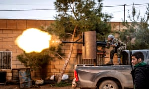 A fighter of the Kurdish People's Protection Units (YPG) fires an anti-aircraft weapon from Tel Tawil village in the direction of Isis fighters.