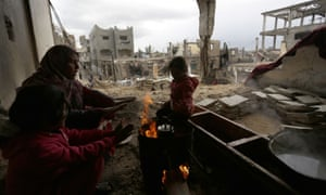 A Palestinian woman and her children warm up around woodfire as they sit at their house that was damaged in Israeli shelling during a 50-day war in the summer of 2014, on February 20, 2015, during a major blizzard of winter in the northern Gaza Strip town of Beit Hanun.