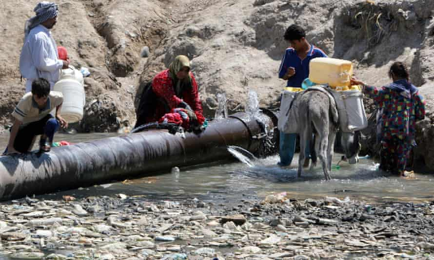 Iraqis fill drinking water and wash clothes at a broken water pipeline in a Shia district of Sadr City, Baghdad.