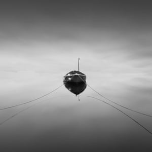 Floating A boat moored appears to float in the reflective sky of a flat clam sea
