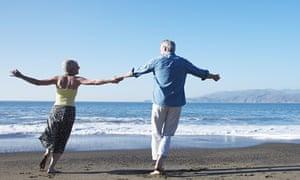 USA, California, Fairfax, Rear view of happy mature couple dancing on beach