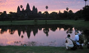 Tourists visit the temples of Angkor, Cambodia, at dawn.