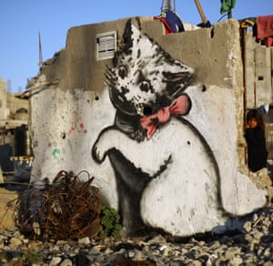 A kitten plays with a ball of mangled steel, in a  mural painted by Banksy in the Palestinian town of Beit Hanun, on the Gaza Strip.