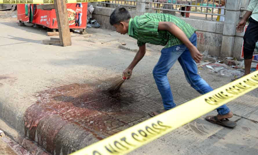 A man cleans up blood at the site where Avijit Roy was killed.