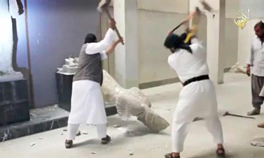 Men use sledgehammers on a toppled statue in a museum at a location said to be Mosul