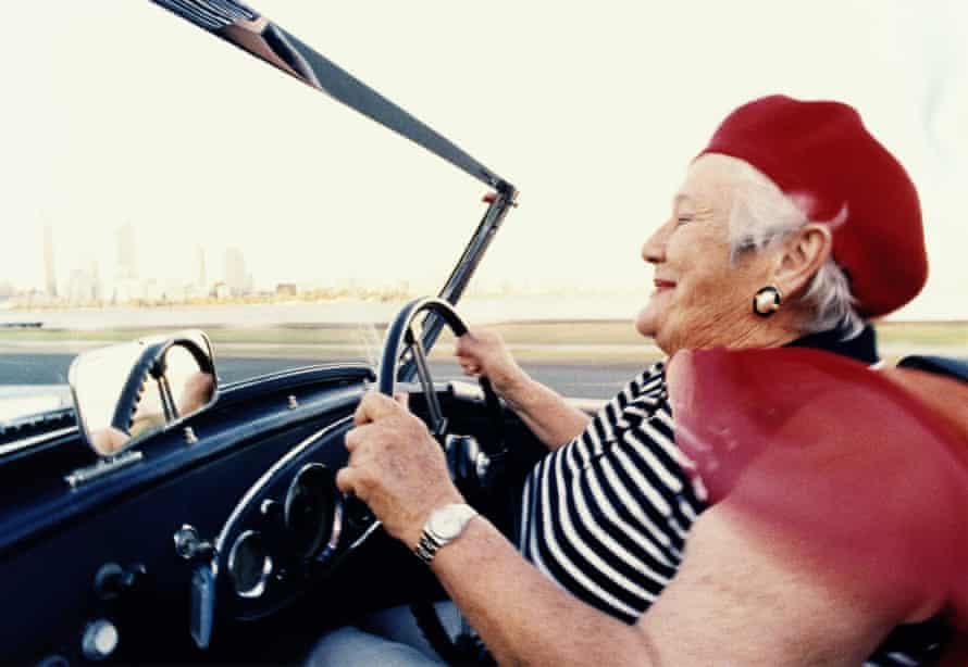 Elderly woman driving convertible sportscar, close-up