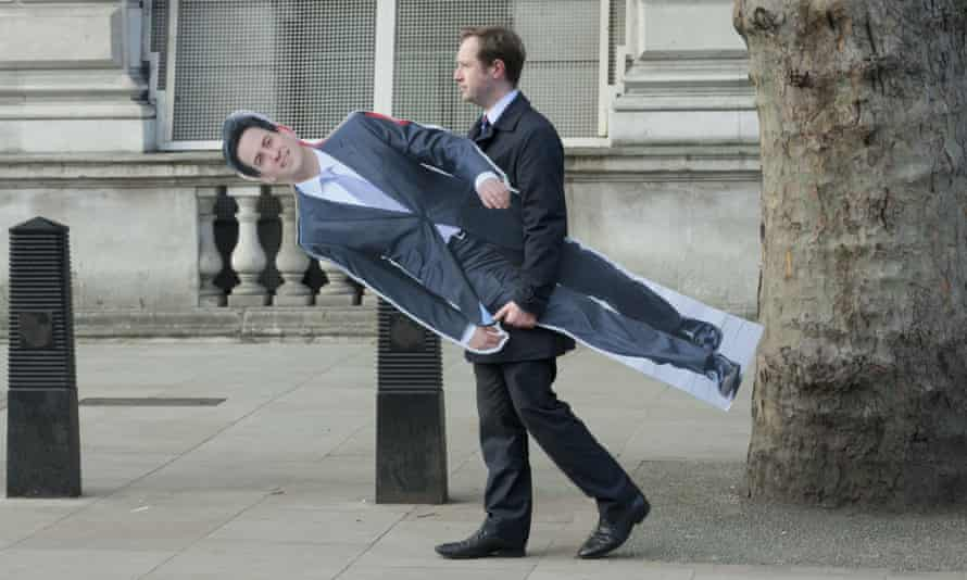 A man carries a cardboard cutout of Ed Miliband outside Downing Street: his campaign strategy is a tough balancing act.