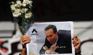 A woman holds up flowers and an picture of late prosecutor Alberto Nisman on the route of his funeral procession.