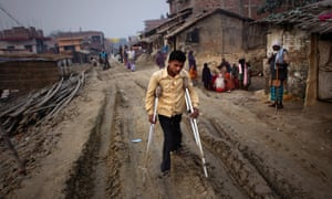 man uses crutches on a dirt track