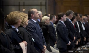 Members of the delegations of Croatia, left, and Serbia, right, stand up as judges enter the court in The Hague.