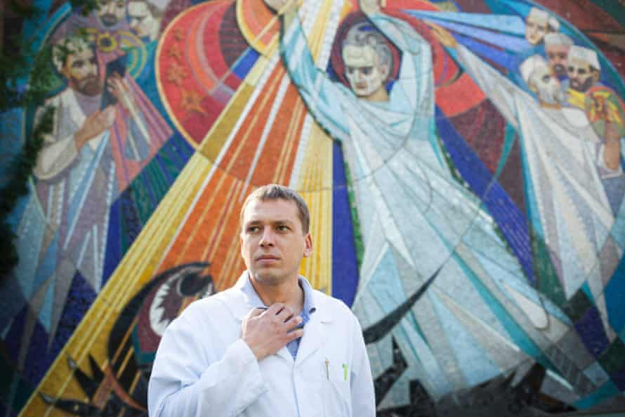 Andrei Semivolos stands outside the institute, in front of a Soviet mural depicting doctors fighting cancer. Photo by Joel van Houdt   longread ukraine