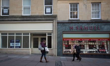 Pedestrians pass an empty shop in Bath. Photograph: Matt Cardy/Getty Images