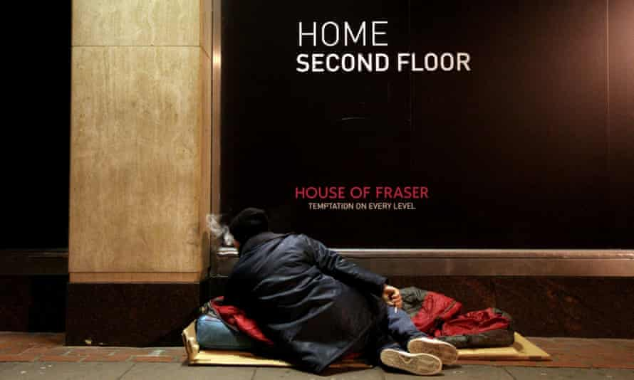 A homeless man rests outside a London department store. The capital has the worst homelessness in England, the report says.