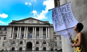 Protester holds a banner outside of the Bank of England, London