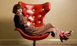Miranda July leaning back in a chair, hands crossed