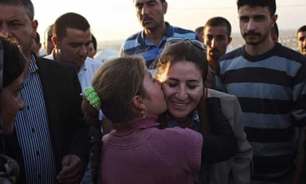 A place of safety: a grateful young Yazidi refugee kisses Vian Dakhil as she visits the Khanke camp.