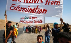 Save our people: displaced Yazidi, who fled the violence in the Iraqi town of Sinjar, hold banners as they take part in a demonstration at the Iraqi-Syrian border crossing in Fishkhabour.