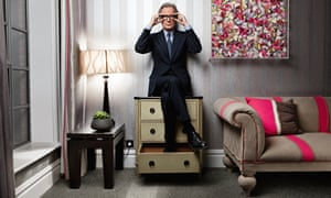 Bill Nighy holdiing his glasses, sitting on a chest of drawers with his feet in a drawer