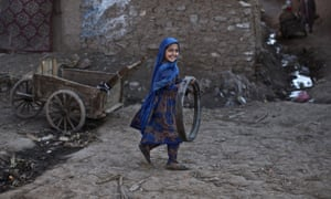 Islamabad, Pakistan An Afghan refugee girl plays with a tire in one of the slums on the outskirts of  the capital