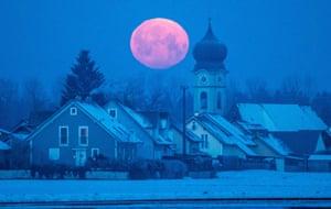 Regensburg, Germany A full moon setting behind the parish church of Schoenach