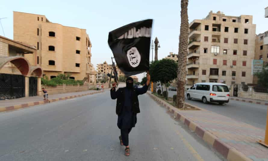 A member of the Islamic State waves a flag in Raqqa, Syria
