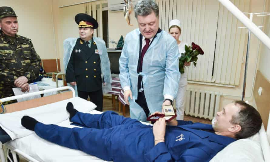 Ukraine's President Poroshenko presents an award to a serviceman wounded during operations against pro-Russia militants in the east of the country during his visit to a military hospital in Kharkiv.