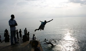 Men dive into the waters of Lake Kivu, Kisegi, Rwanda