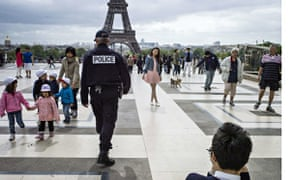 A policeman patrols on Trocadero Square with the Eiffel Tower in the background
