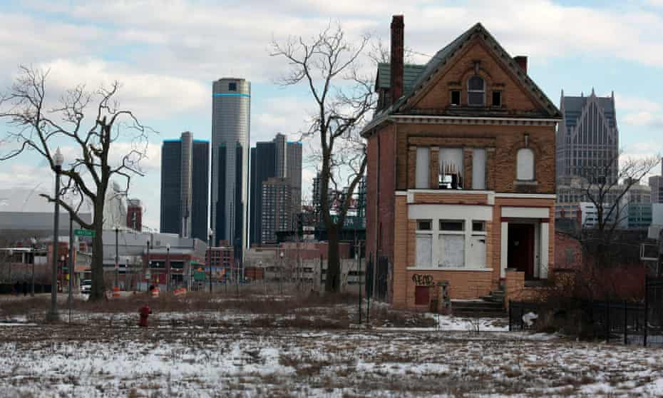 A boarded up house in Brush Park with downtown Detroit behind it