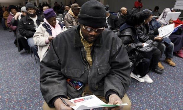 David White pores over paperwork at Detroit's Cobo Center along with hundreds of others waiting for their foreclosure cases to be heard on 29 January 2015.