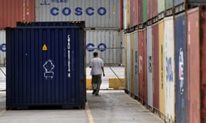 A man walks between containers at the port of Piraeus, near Athens.