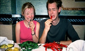 A couple eating chillies.