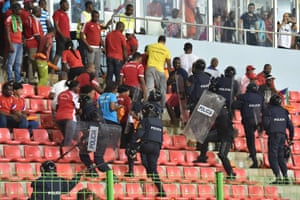 Policemen evacuate a tribune after trouble flared in the stands.