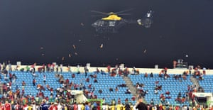 A police helicopter flies low over the stadium as play remains interrupted.