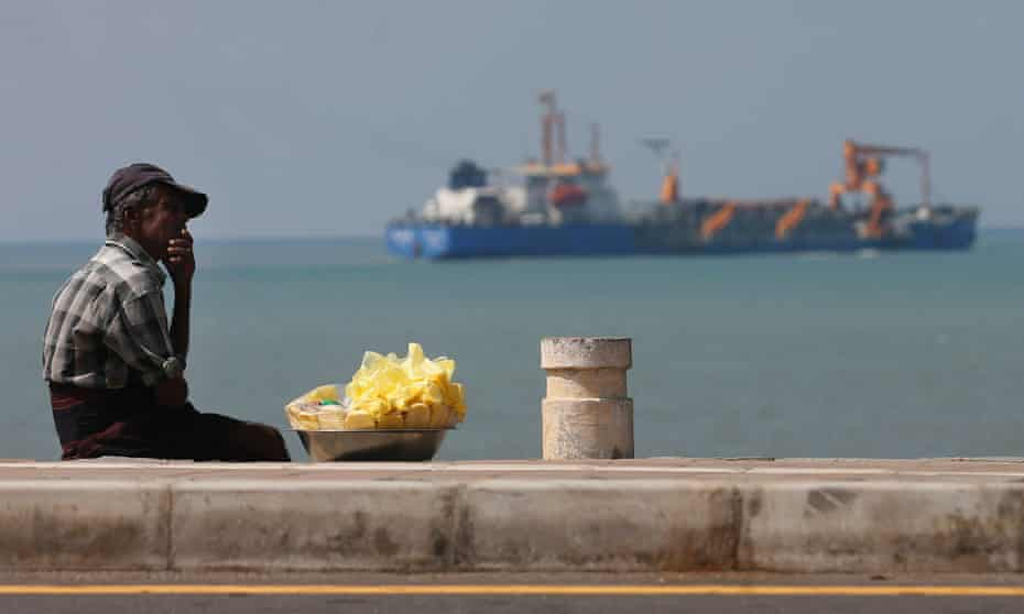A vendor rests next to the Colombo Port City project.