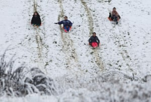 A group of girls slide down a snow-covered slope after a snowstorm as cold weather hit central Europe