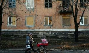 Woman with pram walk past buildings damaged from shells or gunfire in Kommunar