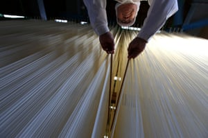 Tatsuno, Japan Somen maker, Yoshinobu Izuhara, uses chopsticks to stretch drying Ibonoito somen noodles - wheat noodle, served either cold with dipping sauce or hot in broth. Noodle production in Tatsuno city dates back approximately 600 years, and are some of the best in Japan