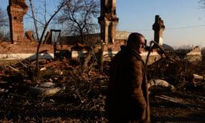 A man walks past damaged buildings in Kommunar