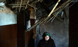 A woman stands in her damaged apartment.