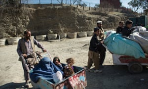 Afghanistan, Torkham, February 5, 2015 Family of Abdul Qader (left), spontaneous refugees, just crossed the border into Afghanistan. They returned after harassment by the authorities of Pakistan. Behind the fence on the hill lays Pakistan.