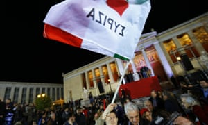 A member of the crowd waves a Syriza flag in Athens, Greece