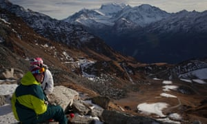 Skiers rest on a mountain overlooking snow-free slopes. Unusually warm, dry weather has ski resorts worldwide on edge.
