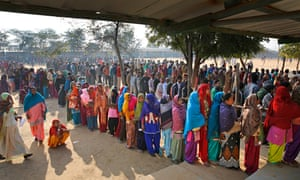 People wait in a queue to cast their votes at a polling booth in New Delhi
