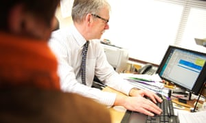 Male GP in patient consultation, looking up digital medical records