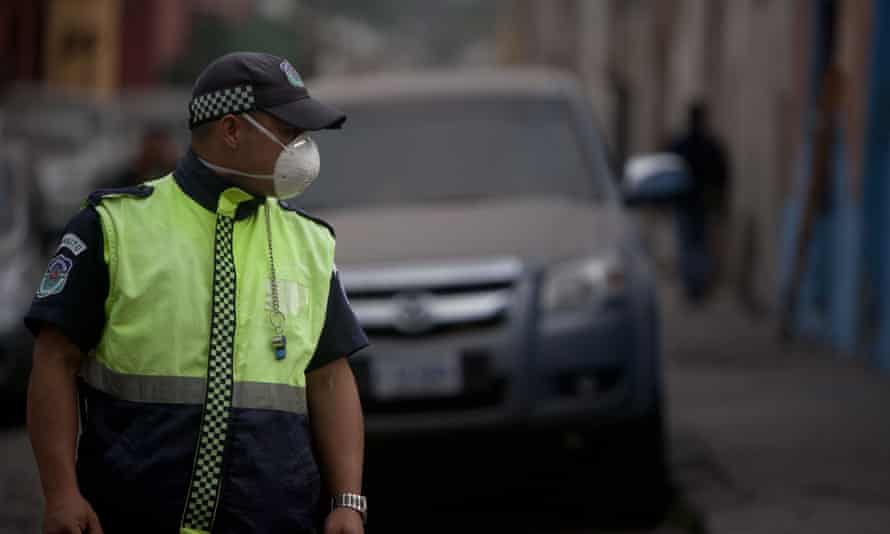 A traffic police officer covers his face with a mask as he works on a street covered covered with ash.