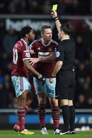 Alex Song is shown a yellow card by referee Mark Clattenburg as Kevin Nolan looks on.