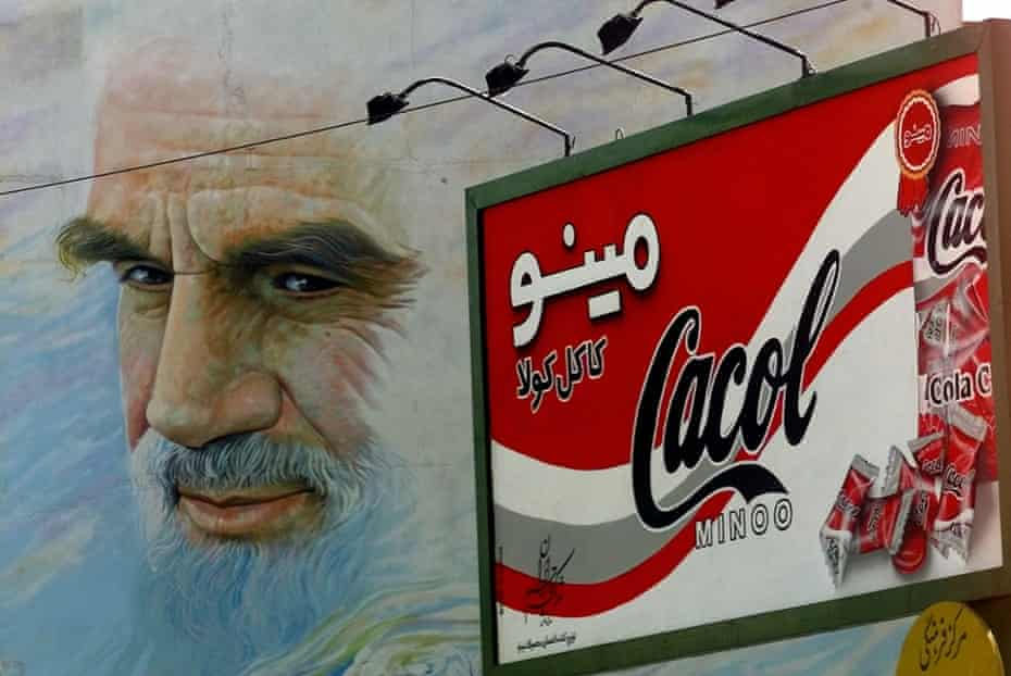 A giant mural of the late Ayatollah Khomeini appears to gaze past an advertisement for Cacol, a candy that mimics American soft drink Coke above a major intersection in Tehran, Iran.